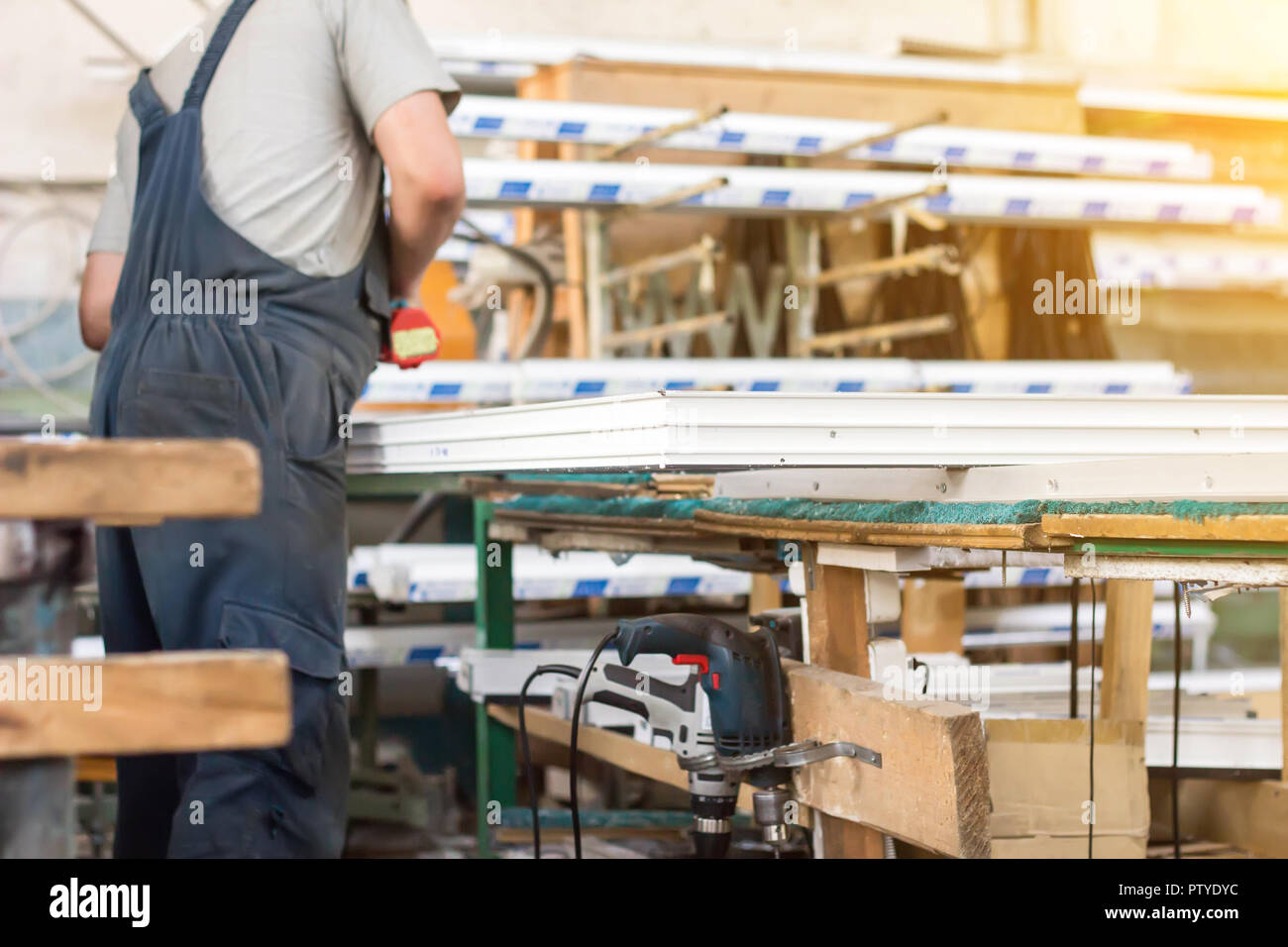 Production of pvc windows, a man collects a pvc window, a screwdriver, worker - Stock Image