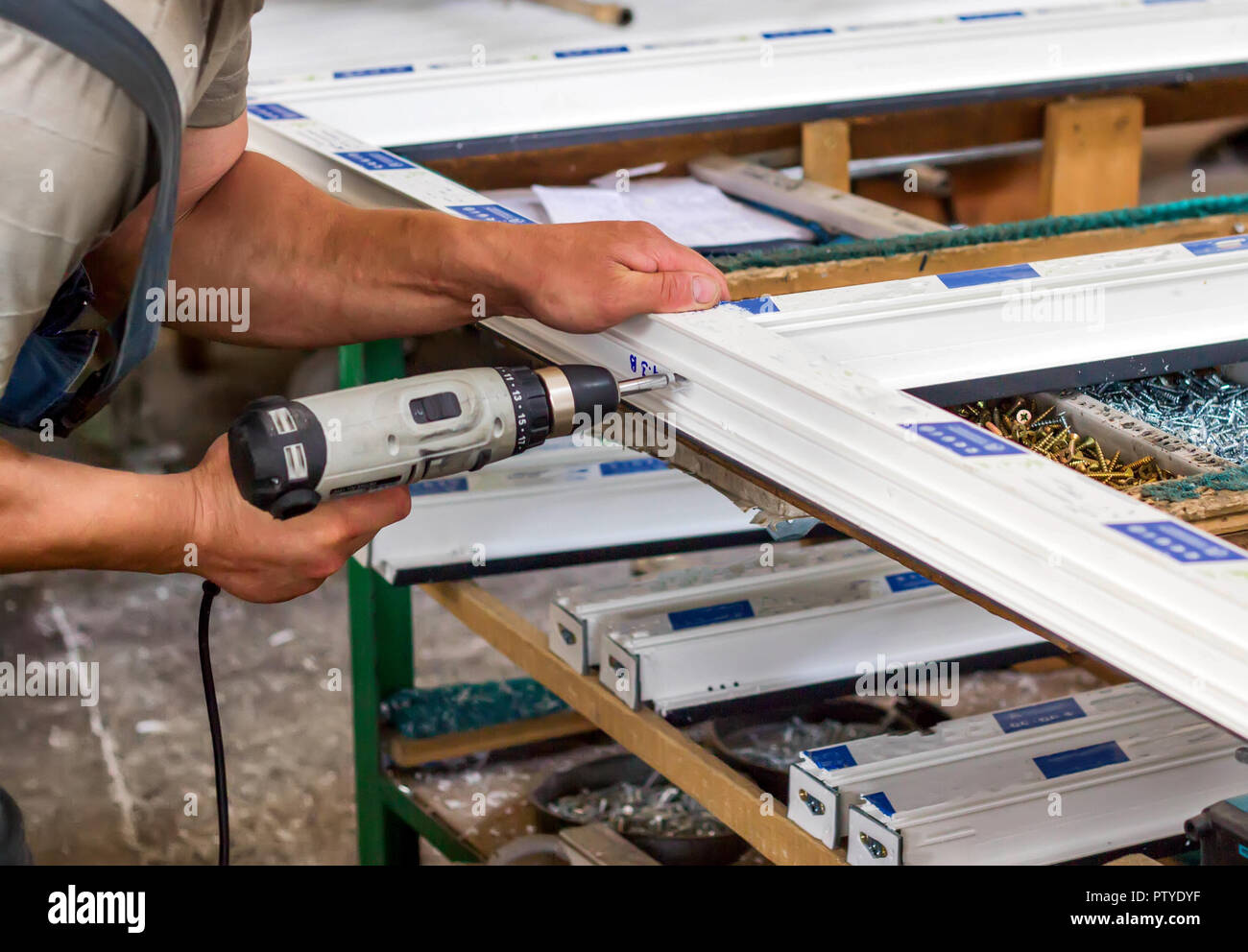 Production of pvc windows, a man screws a screwdriver into a pvc window, close-up, windows pvc Stock Photo