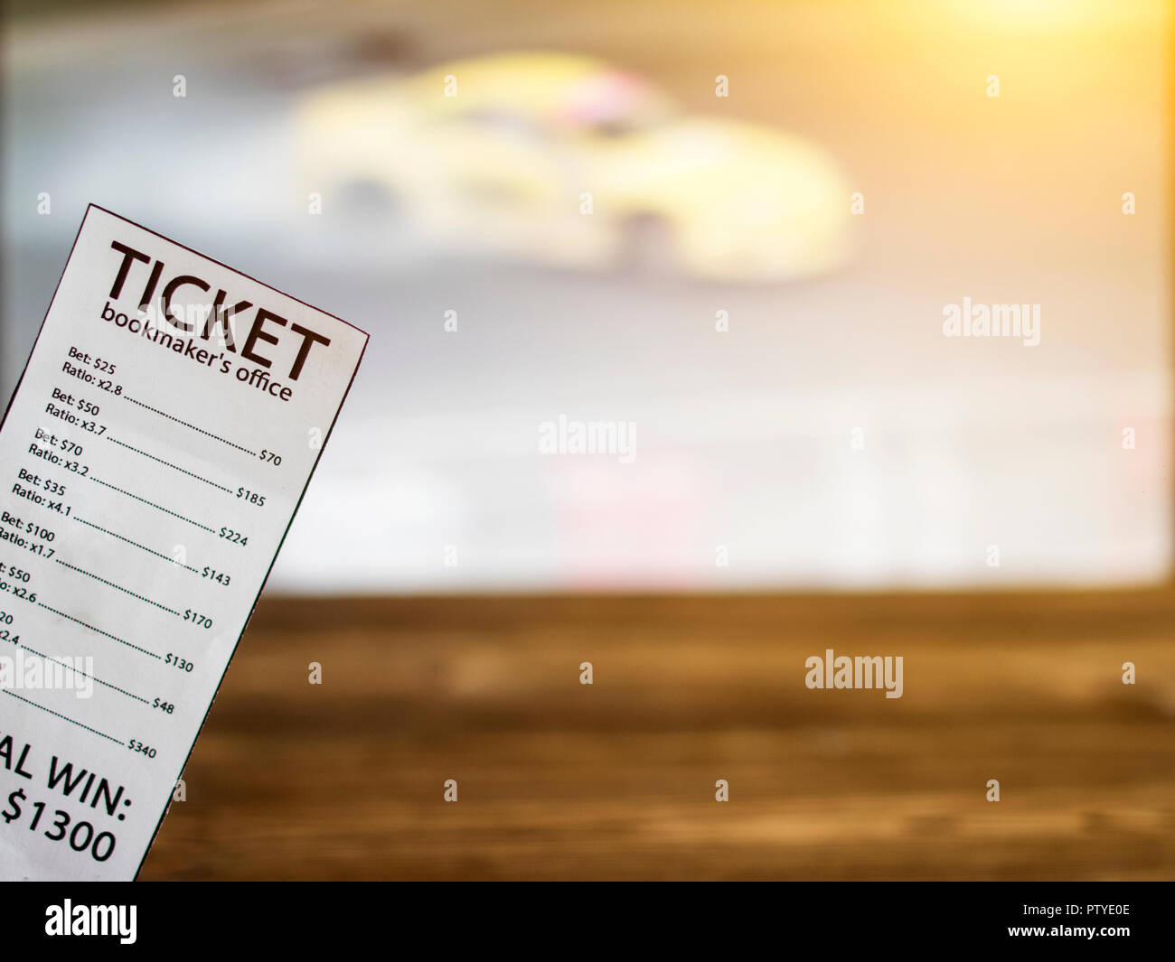 Bookmaker ticket on the background of the TV on which show drift on cars, sports betting, drift - Stock Image