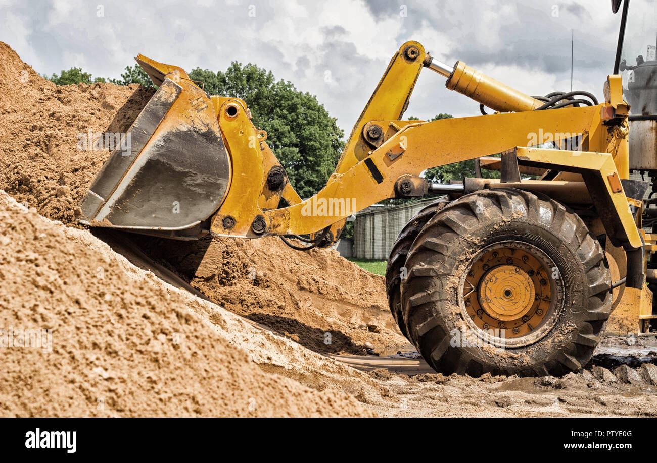 Yellow tractor loader is picking up a bucket of earth, mechanical, ladle with earth Stock Photo