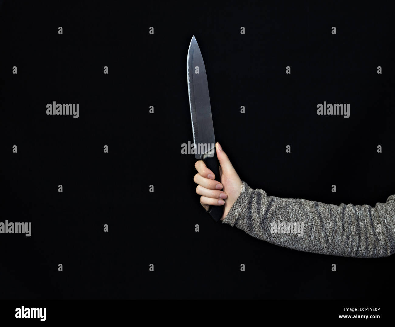 Hand of a girl with a knife on a black background, close-up, knife - Stock Image