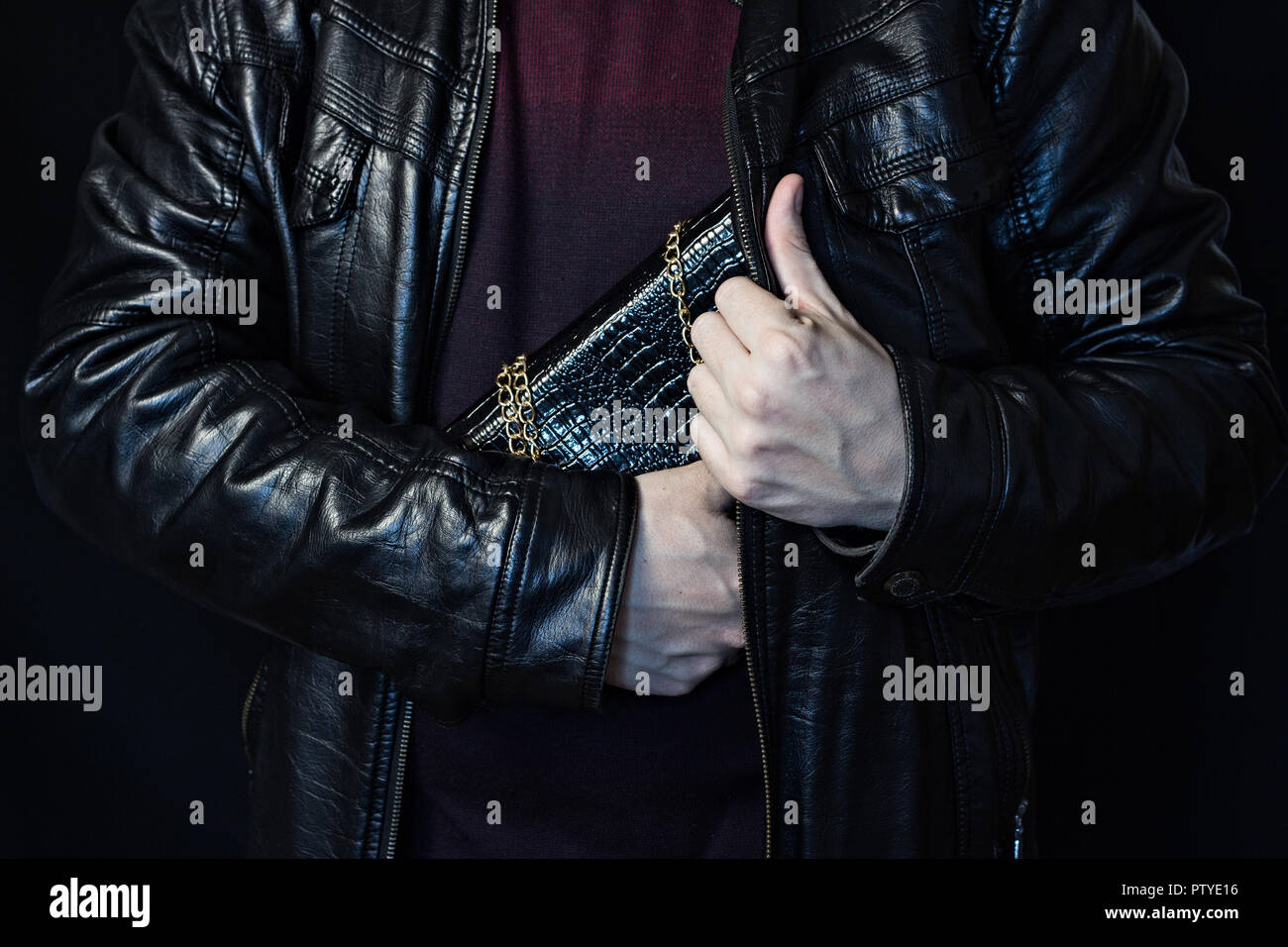 A man hides a woman's handbag in his bosom, the theft of a handbag, a black background, Theft of bags - Stock Image