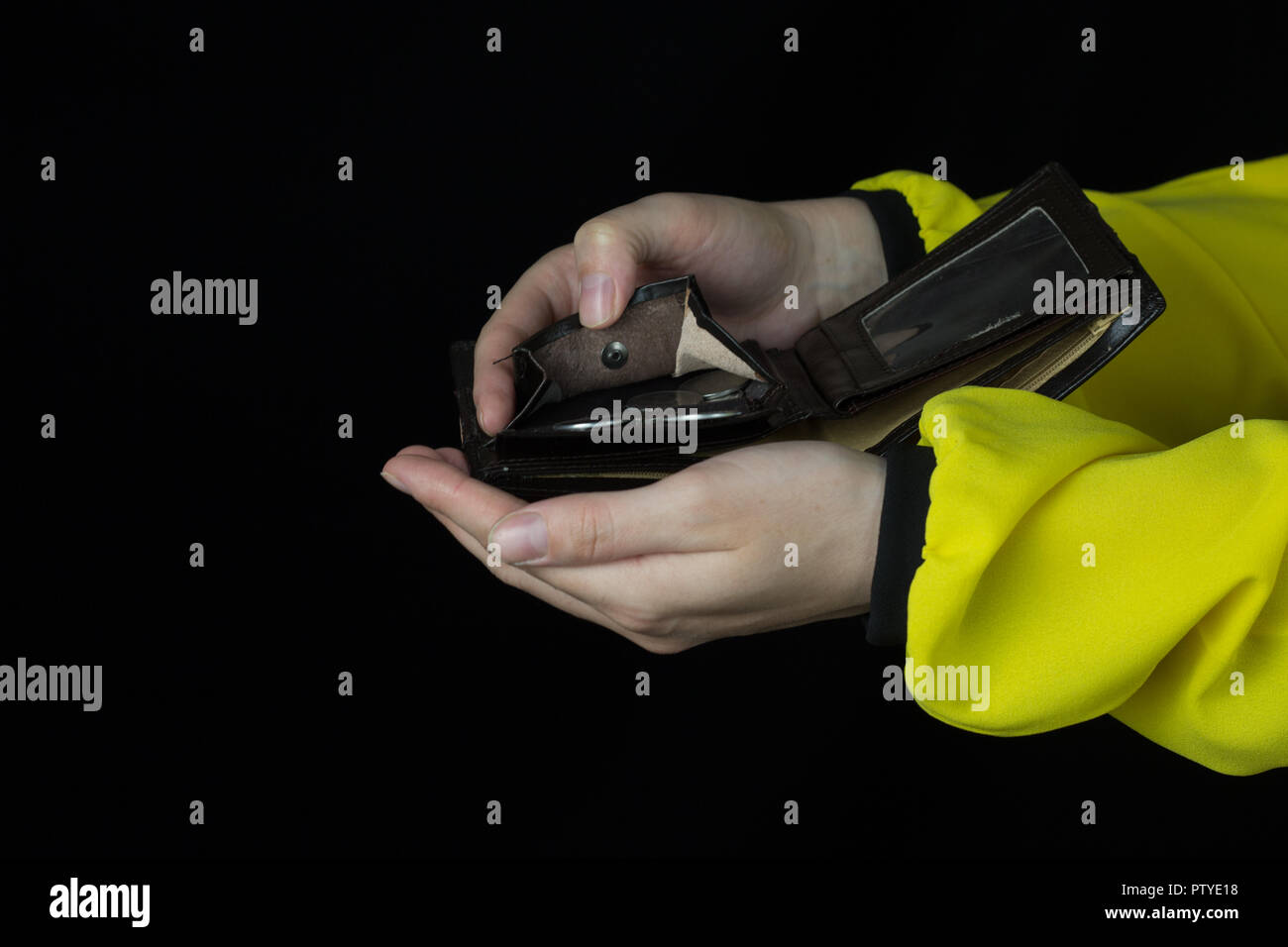 Girl pouring coins out of a purse, close-up, black background, money - Stock Image