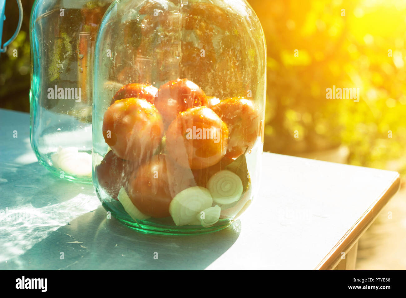 Closure of conservation on the table with tomatoes, sun - Stock Image