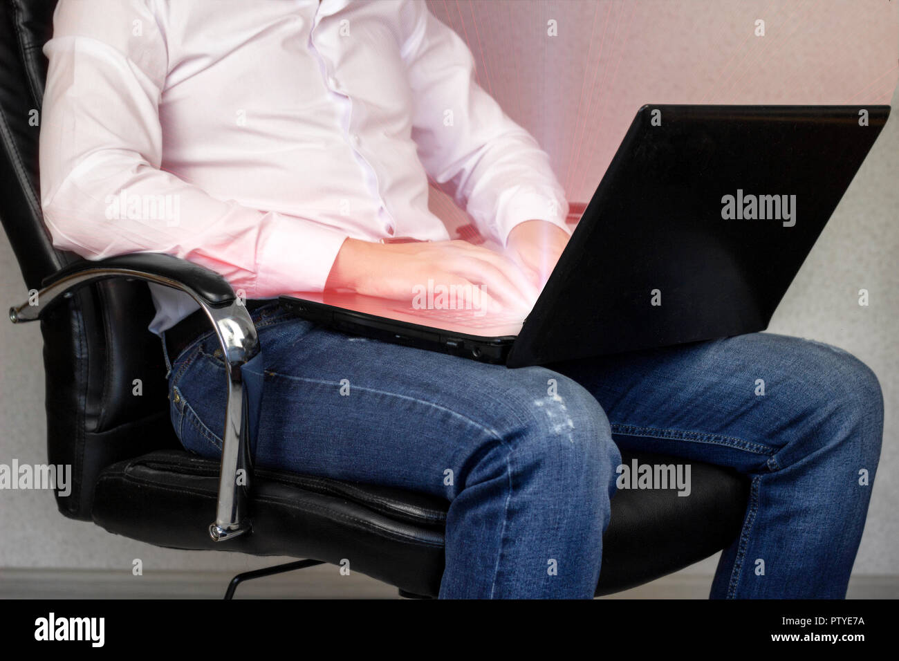 The man is working behind the laptop from the screen is harmful radiation, emitting - Stock Image