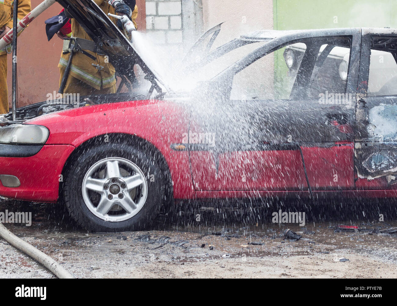 Firefighters extinguish a burning car with water, fire, extinguish - Stock Image