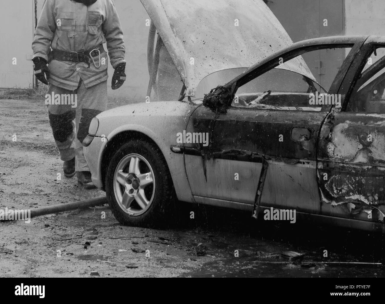 Firefighters extinguish a burning car with water, fire, extinguish, black and white - Stock Image