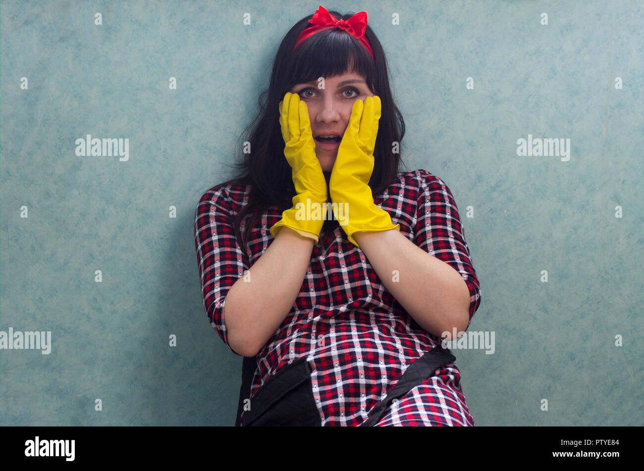 Brunette girl in yellow gloves with open mouth - Stock Image