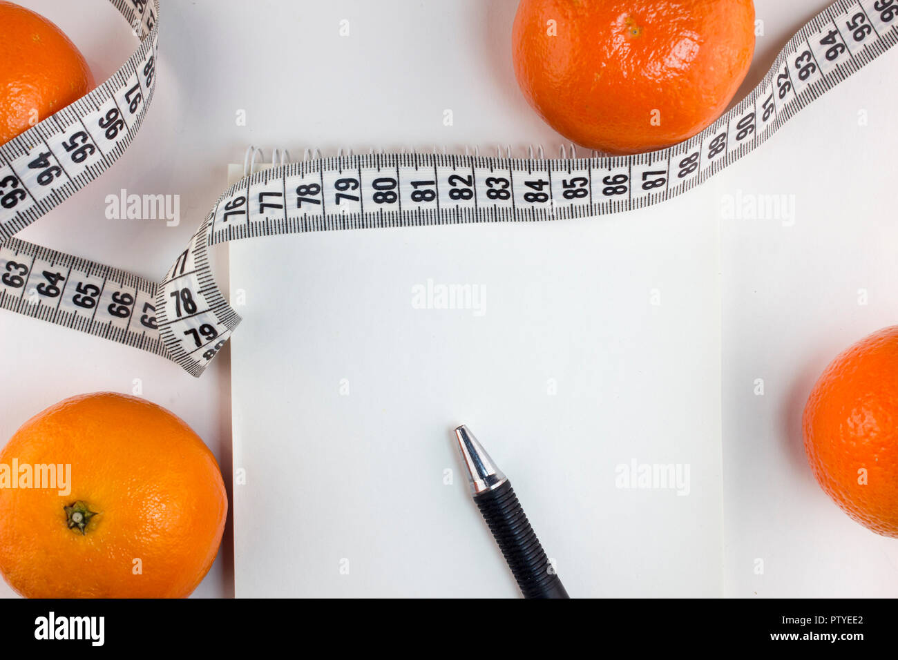 Mandarins, notepad, centimeter tape on a white background - Stock Image
