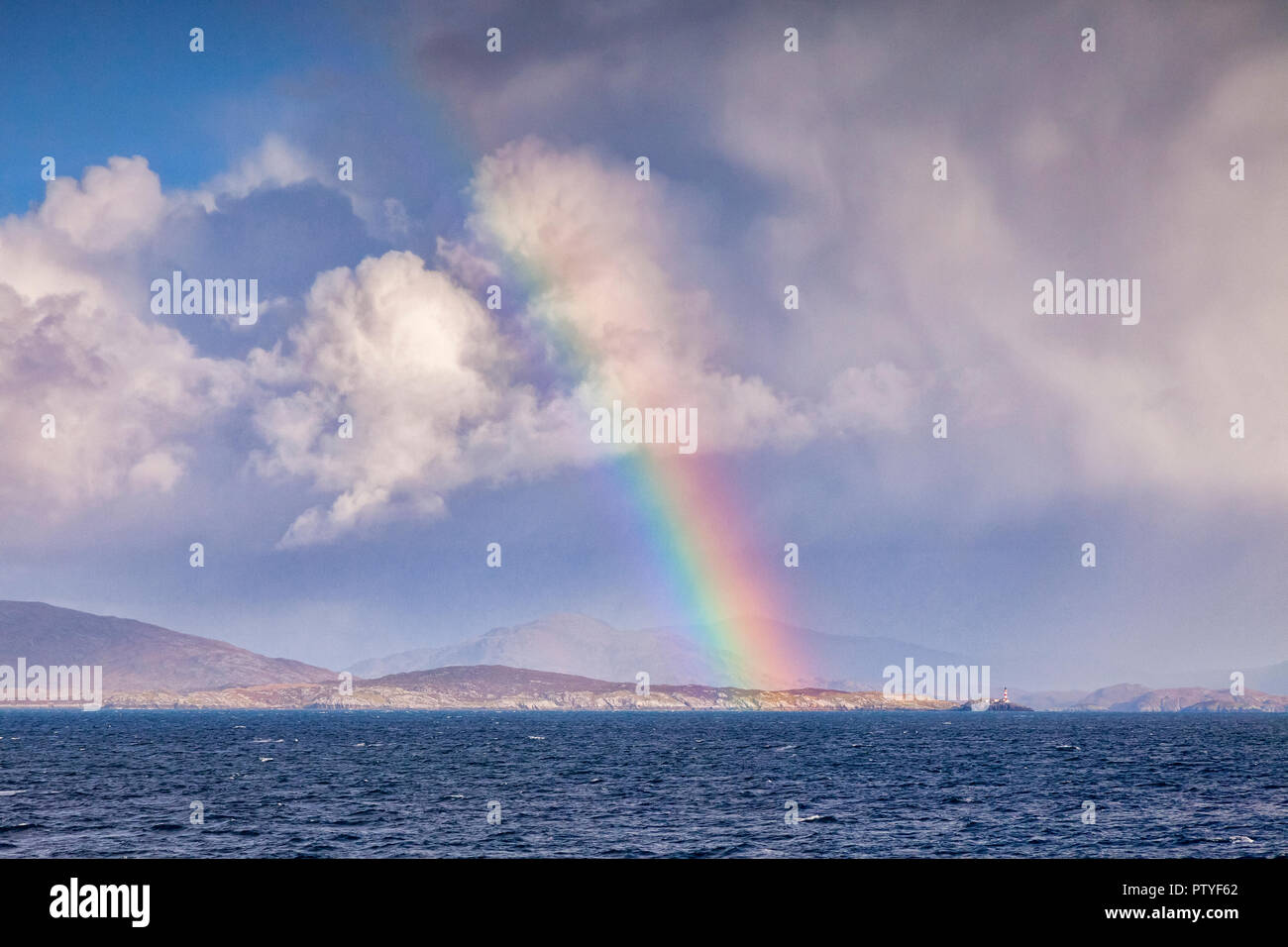 View from the sea of rainbow and Eilean Glas lighthouse approaching the port of Tarbert on the Isle of Harris, Outer Hebrides,Scotland,UK. - Stock Image