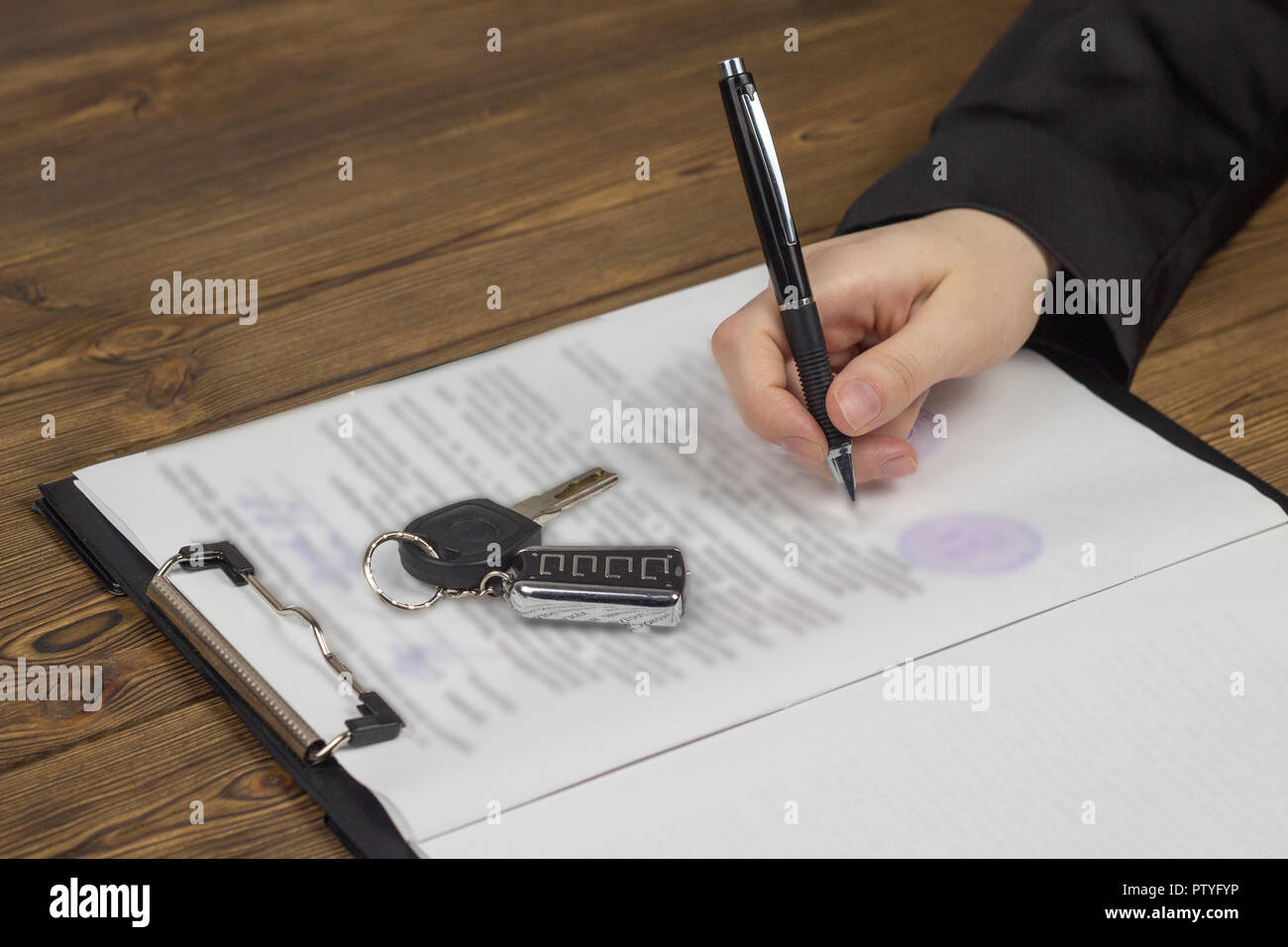 Buying a car, hand, keys, contract, seal, pen - Stock Image