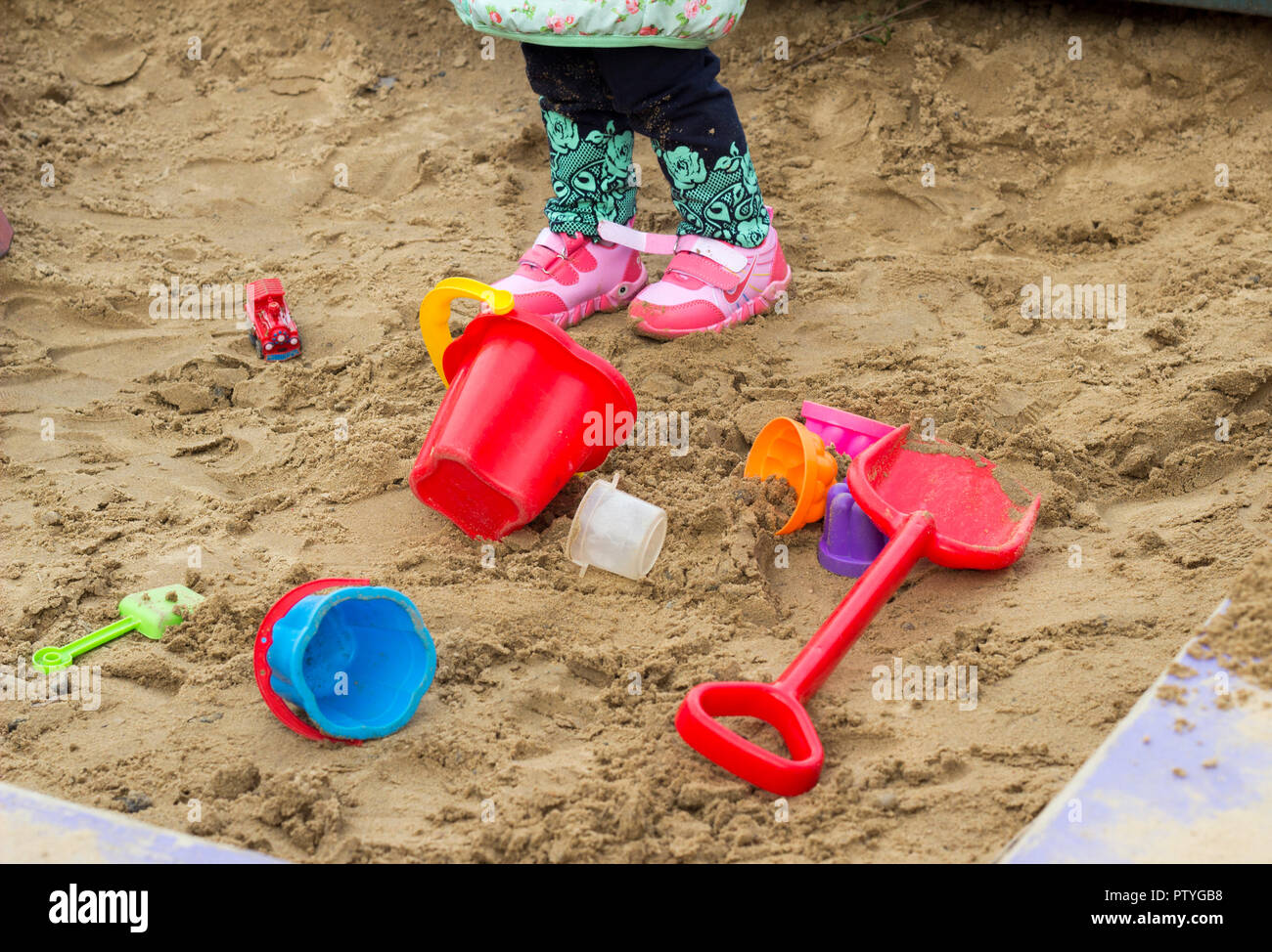 Children's toys in the sandbox and children's legs - Stock Image