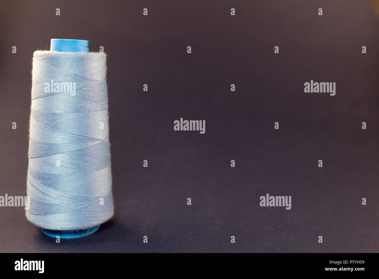 Blue skein of thread on a blue background - Stock Image