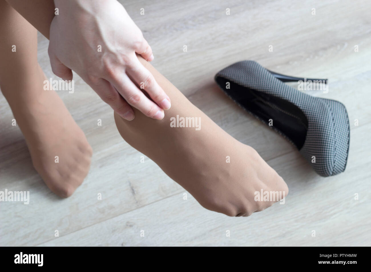 A girl clings to her leg, fatigue from her heels, high heels, pain in her legs, close-up - Stock Image