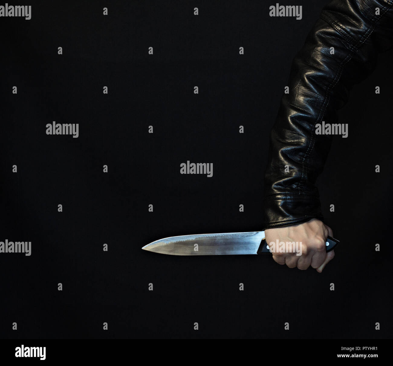 A man's hand in a jacket with a knife on a black background - Stock Image