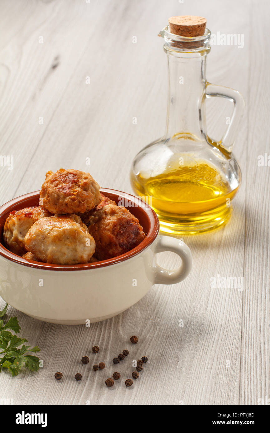 Fried meat cutlets in white ceramic soup bowl, glass bottle with sunflower oil, branch of fresh parsley and black peppercorn on grey wooden boards Stock Photo