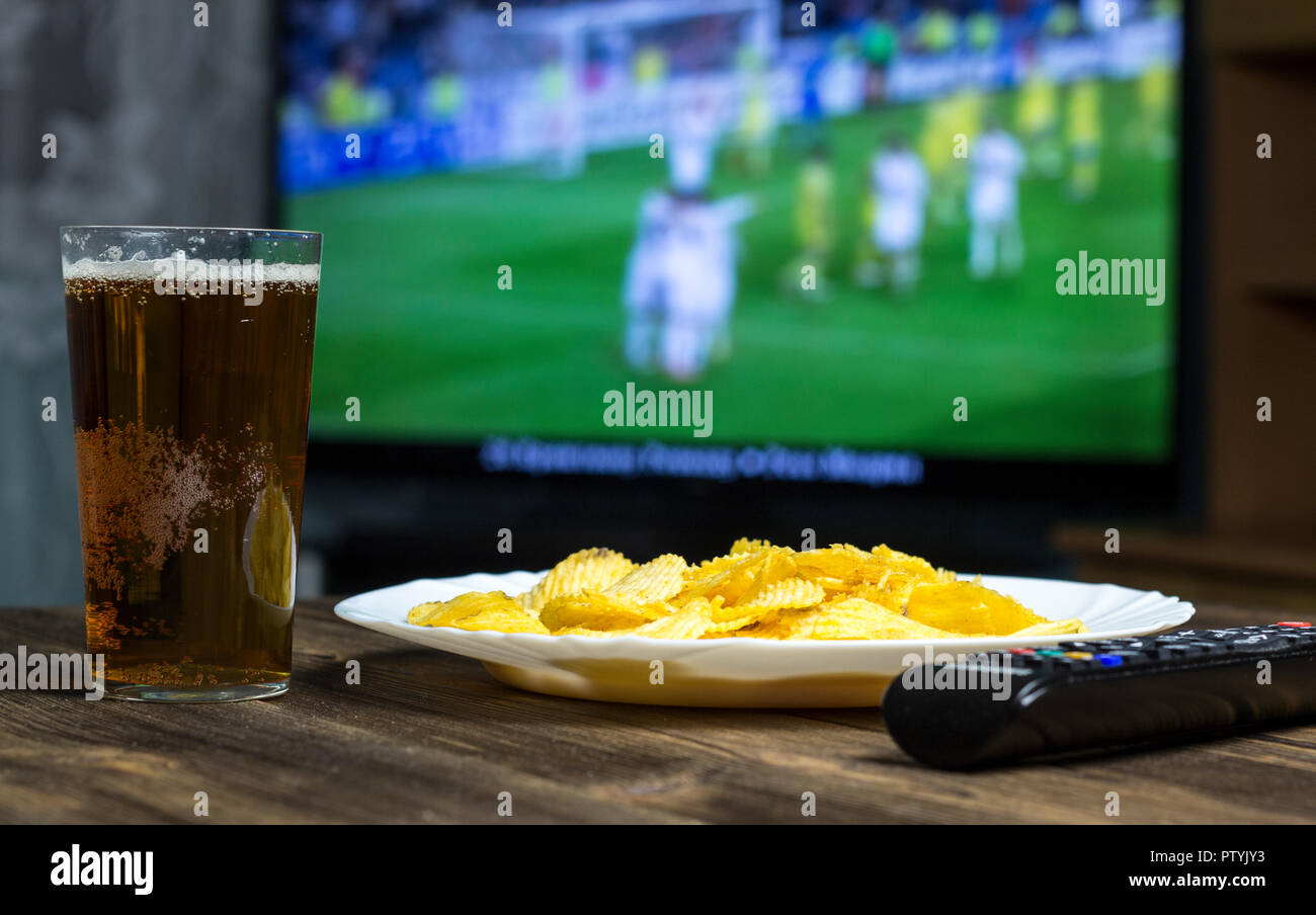 Beer, chips, TV remote control and TV in which show football - Stock Image
