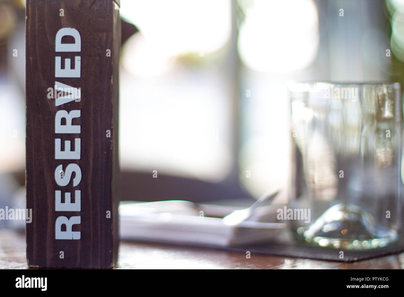 Reserved wooden Card Plate on the Table with Blurry background. Reservation Seat at restaurant. - leisure, people and service concept. - Stock Image