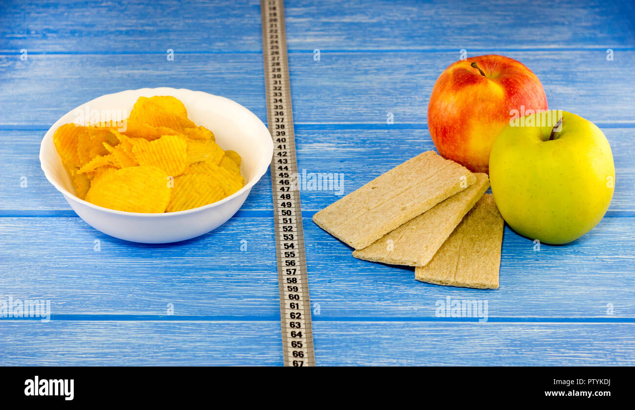 Chips apples breads centimeter tape on a blue wooden background - Stock Image