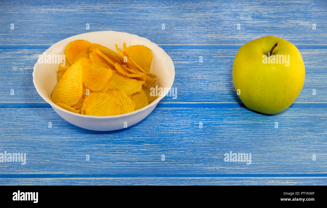 Chips and a green apple on a blue background - Stock Image