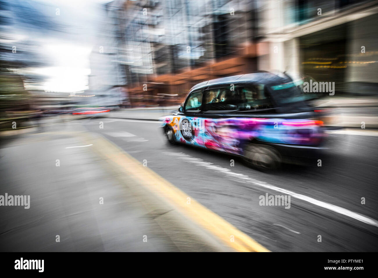 British taxi cab speeding in central London. Deliberately blurred to convey speed. Motion blur effect. - Stock Image