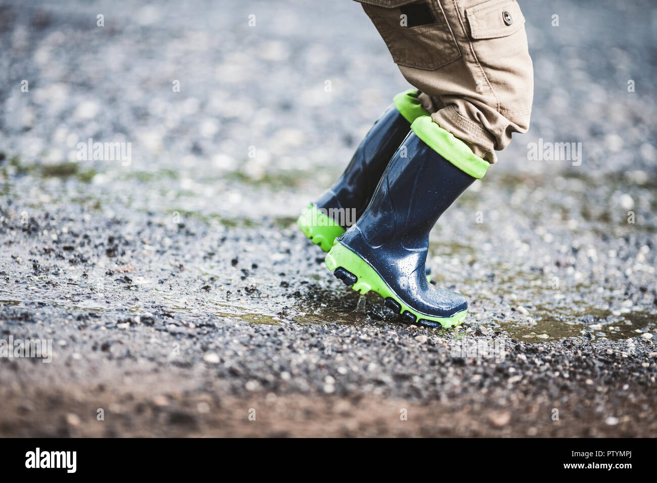 Close up on toddler wearing rubber boots in rainy weather Stock Photo