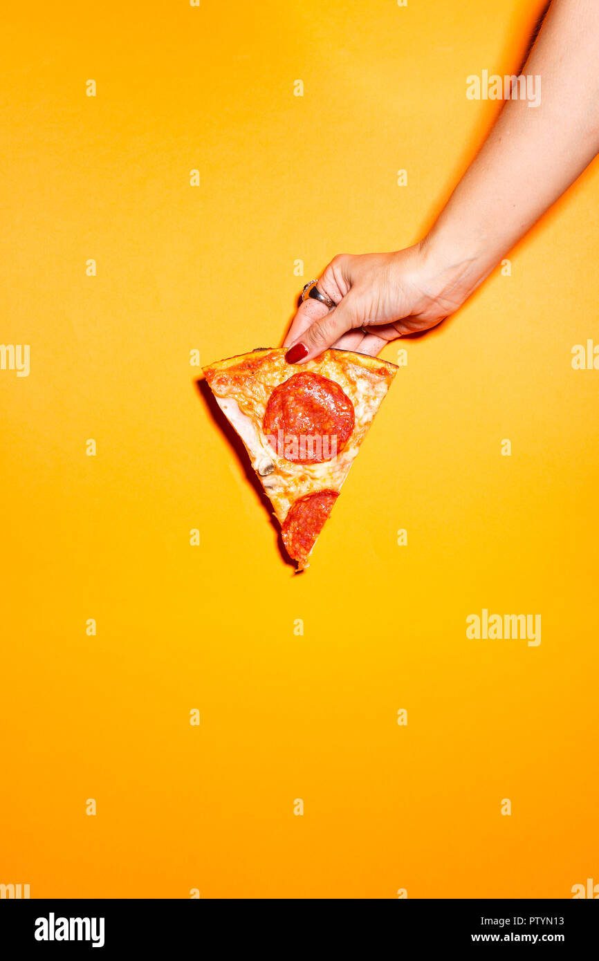 Female hand holding slice of pizza against orange background. - Stock Image