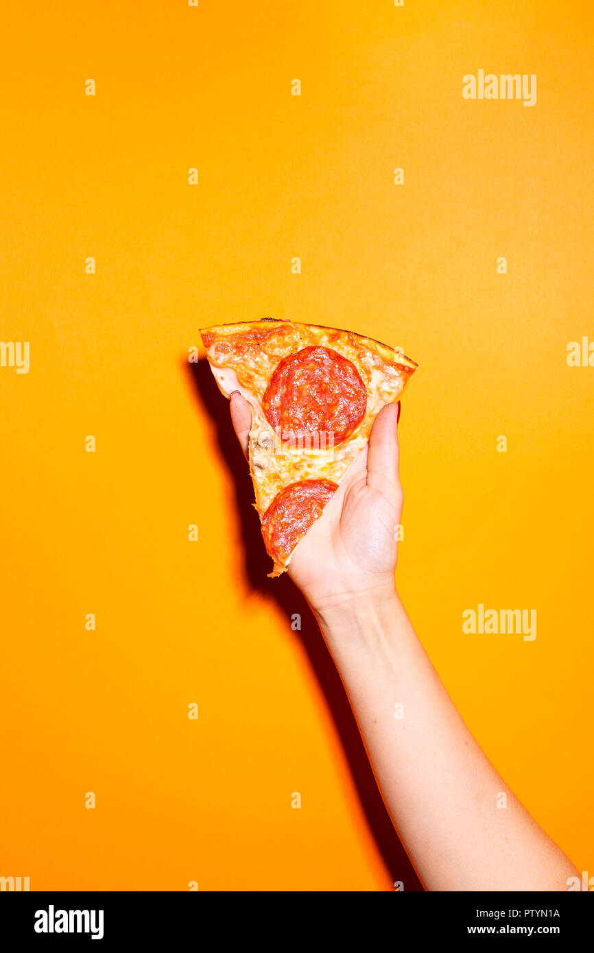 Hand holding slice of pizza isolated on orange background. - Stock Image