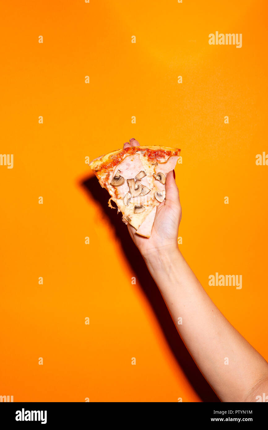 Hand holding mushroom pizza against orange background. - Stock Image
