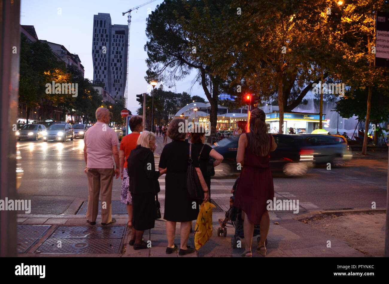 three widows and a woman with buggy wait to cross the street in tirana albania - Stock Image