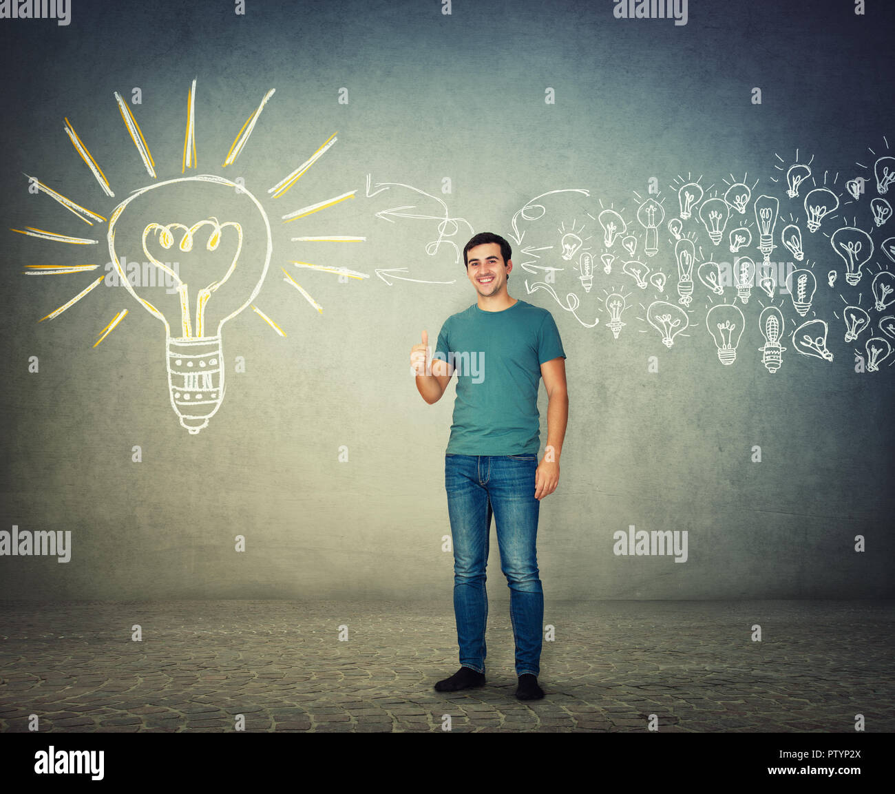 Full length portrait of smiling casual man showing thumb up as like sign. Business concept pensive boy gathering ideas into a big light bulb. - Stock Image