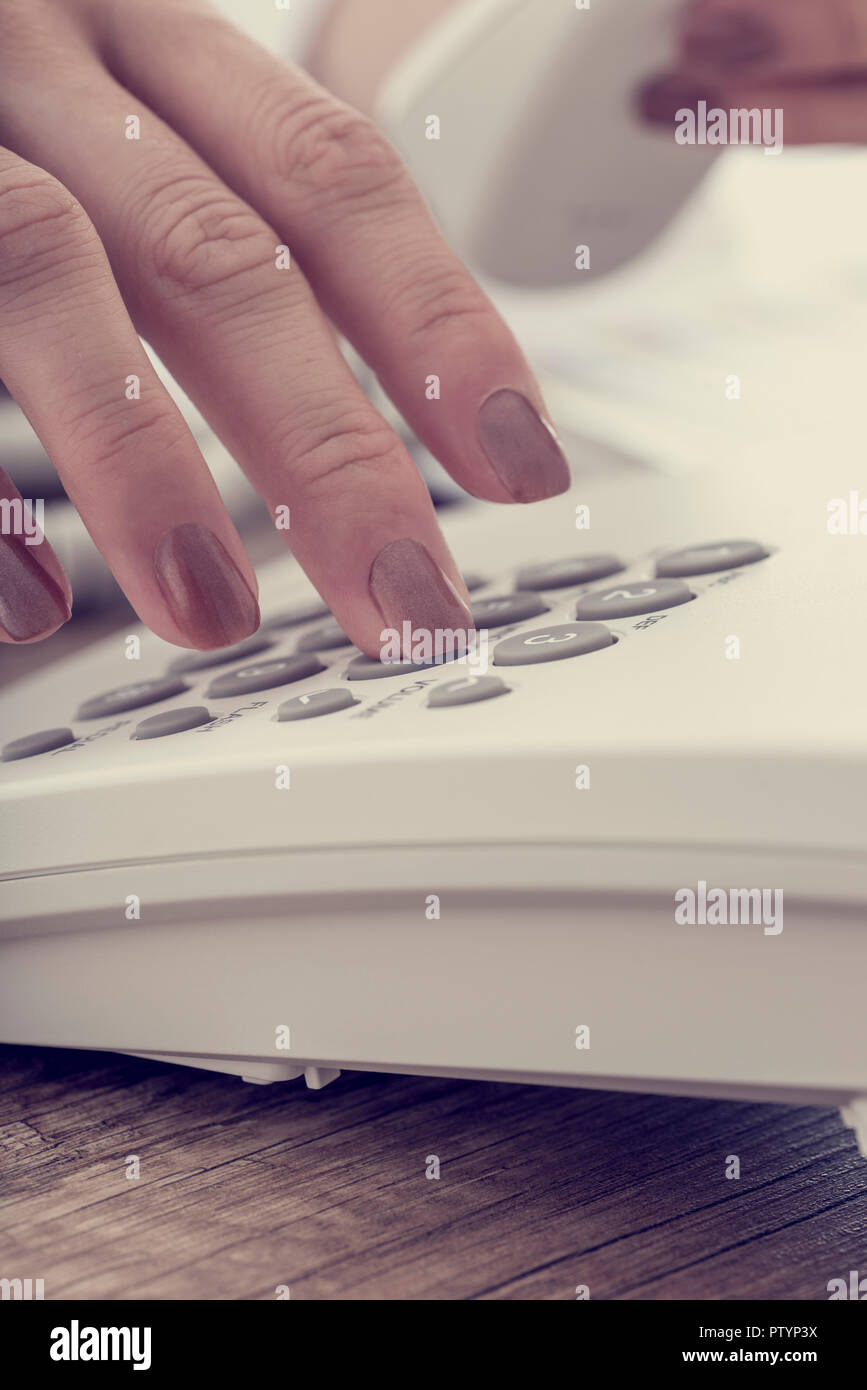 Retro effect faded and toned image of a female hand dialing a telephone number using white landline phone. - Stock Image