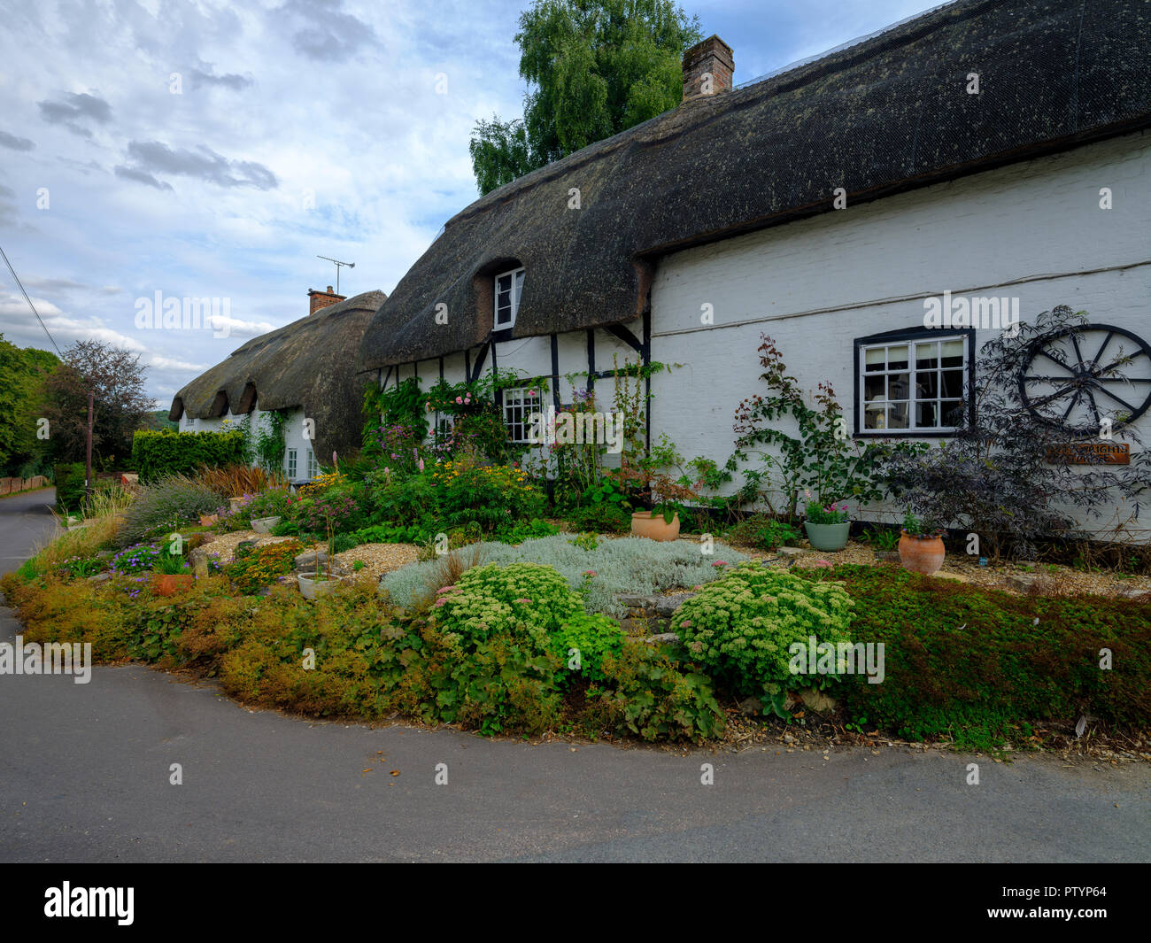 Typical Hampshire country cottage - half timbered and thatched - with pretty front garden in the village of Easton near Winchester in the South Downs  Stock Photo