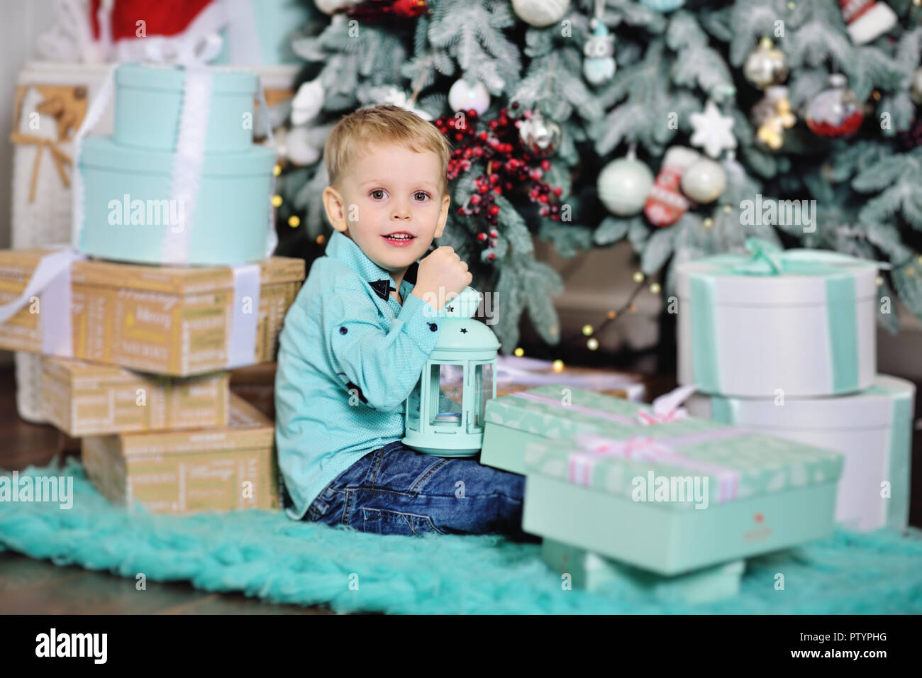 baby boy opens boxes with gifts under the Christmas tree and smiles ...
