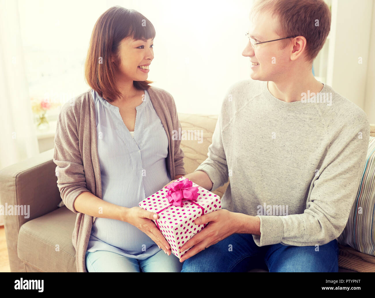 Husband Giving Birthday Present To Pregnant Wife