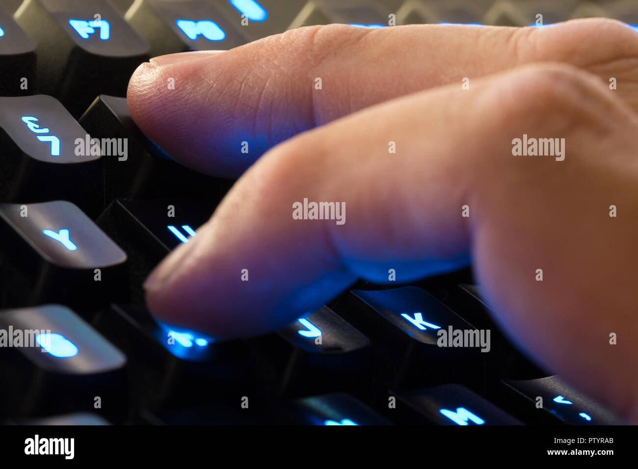 Fingers from the hand of a man typing on a backlit computer keyboard. - Stock Image