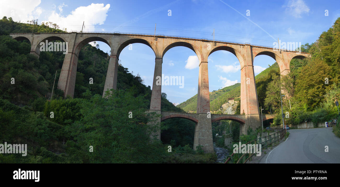 Genova Italy September 15, 2018: old arched railway bridge made with solid brick   in a gorge between two hills Stock Photo