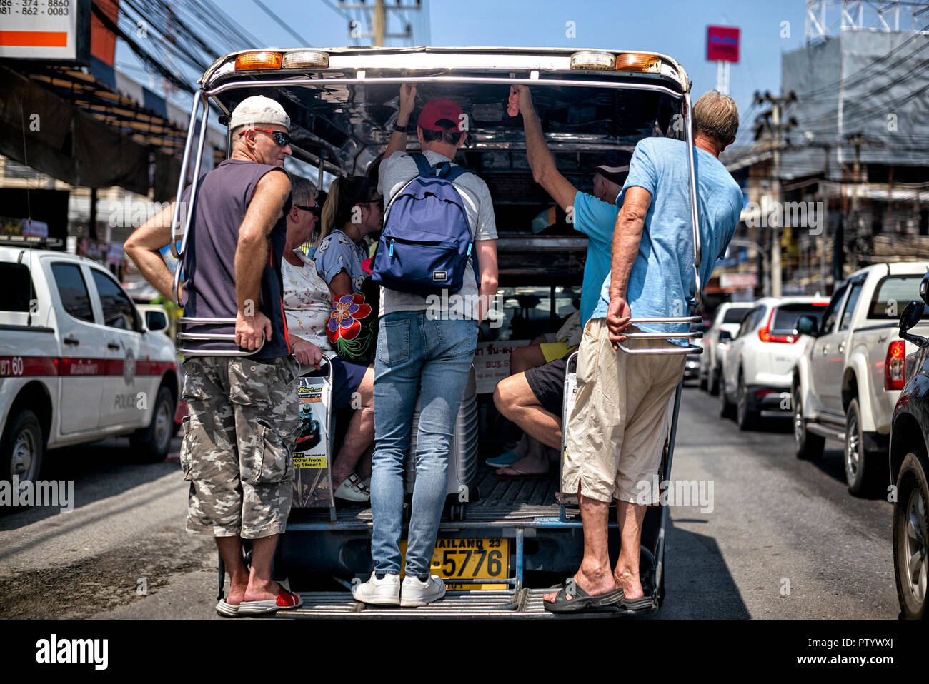 People riding on a Thailand songtheaw public baht bus - Stock Image