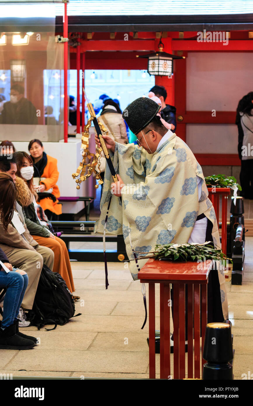 Japanese new year, shogatsu. Shinto Priest, Kannushi, performing a blessing ceremony on people seated inside the Honden at the Ikuta shrine in Kobe. - Stock Image