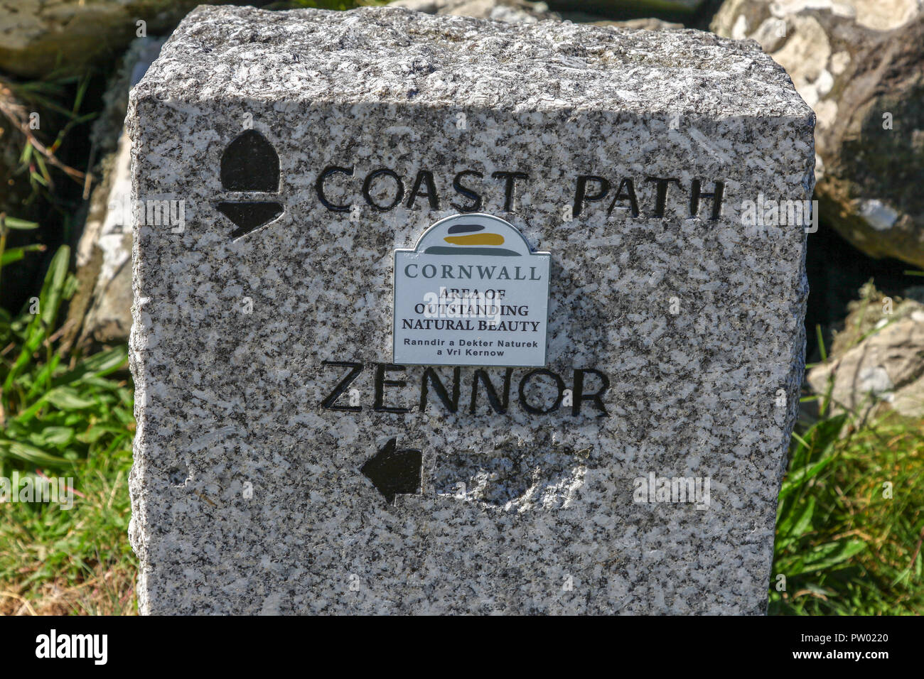 A granite sign post on the South West Coast path saying Cornwall Area of Outstanding Natural Beauty, also in Cornish, St. Ives, Cornwall, England, UK - Stock Image