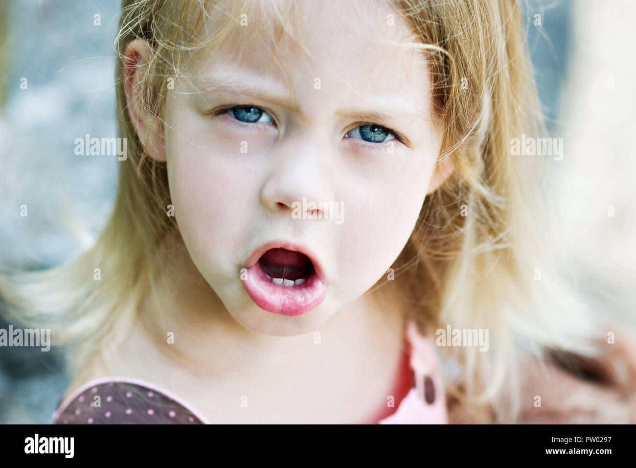 Cute blond child angry and throwing a temper tantrum Stock Photo