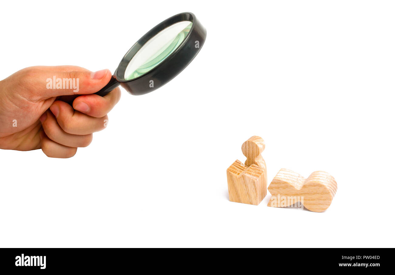 Magnifying glass is looking at a small figure of a man looks out of the remains of a large figure. a way out of the comfort zone. Reincarnation into a Stock Photo