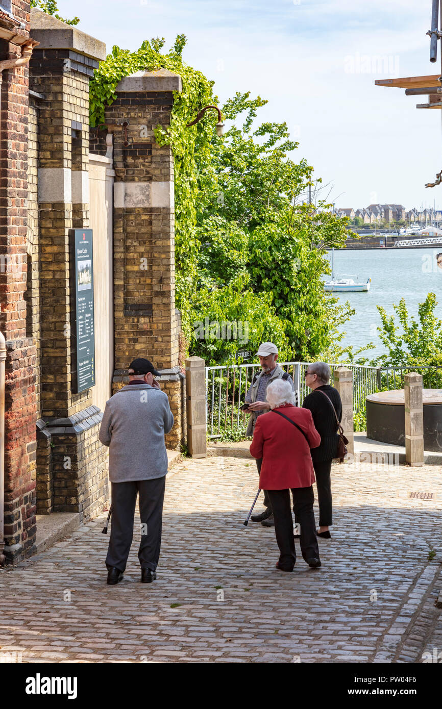 A group of elderly people look at the entry fro Upnor Castle on Upnor High Street, Kent, UK - Stock Image