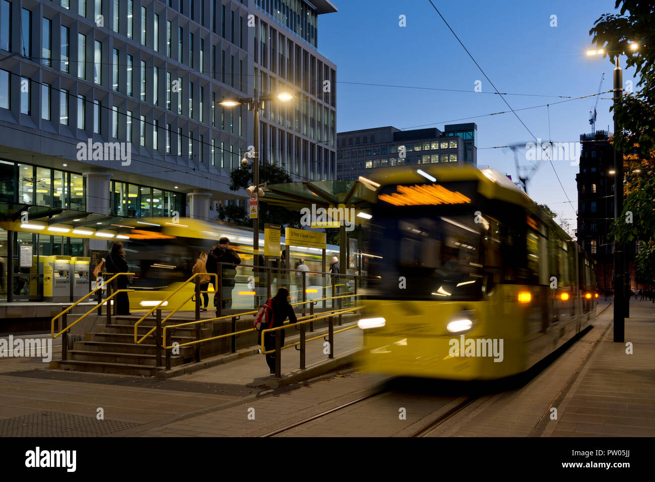 Two Metrolink trams leave St Peter's square stop at night in Manchester City Centre, UK. - Stock Image