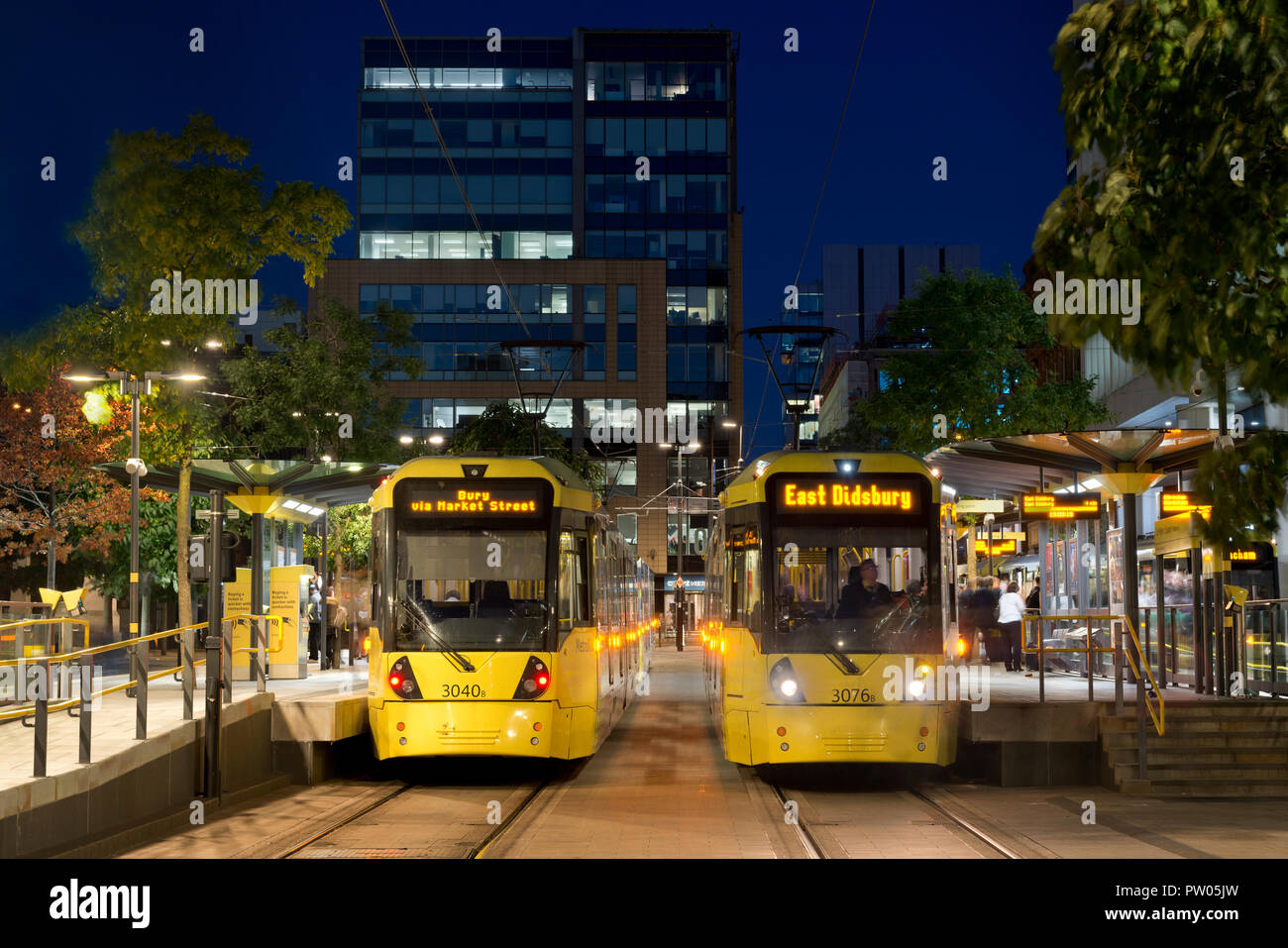 Two Metrolink trams arrive at St Peter's square stop at night in Manchester City Centre, UK. Stock Photo