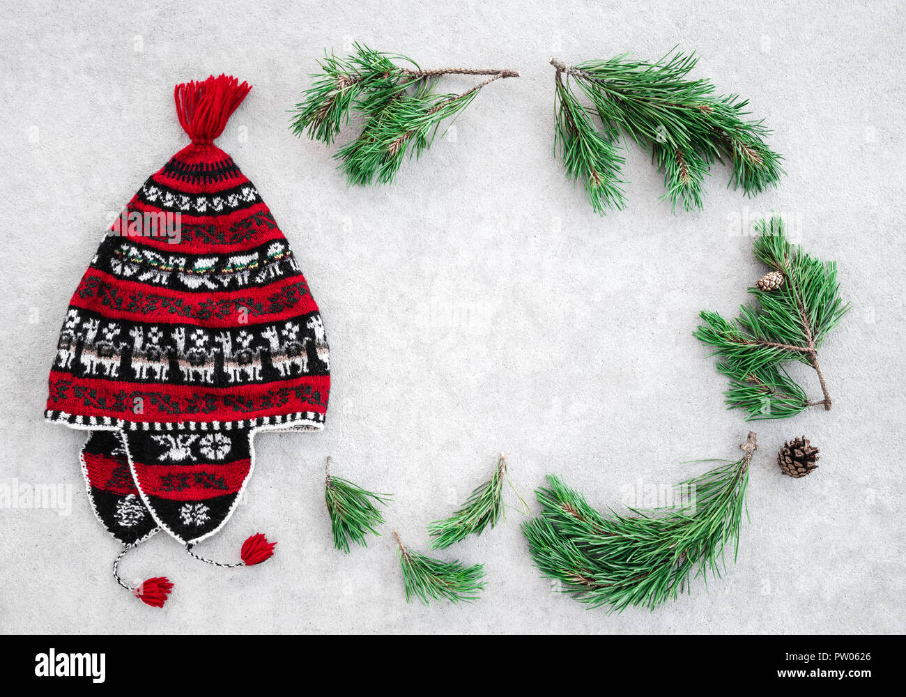 Red knitted winter hat and green pine branches forming a frame, on light gray background. Stock Photo