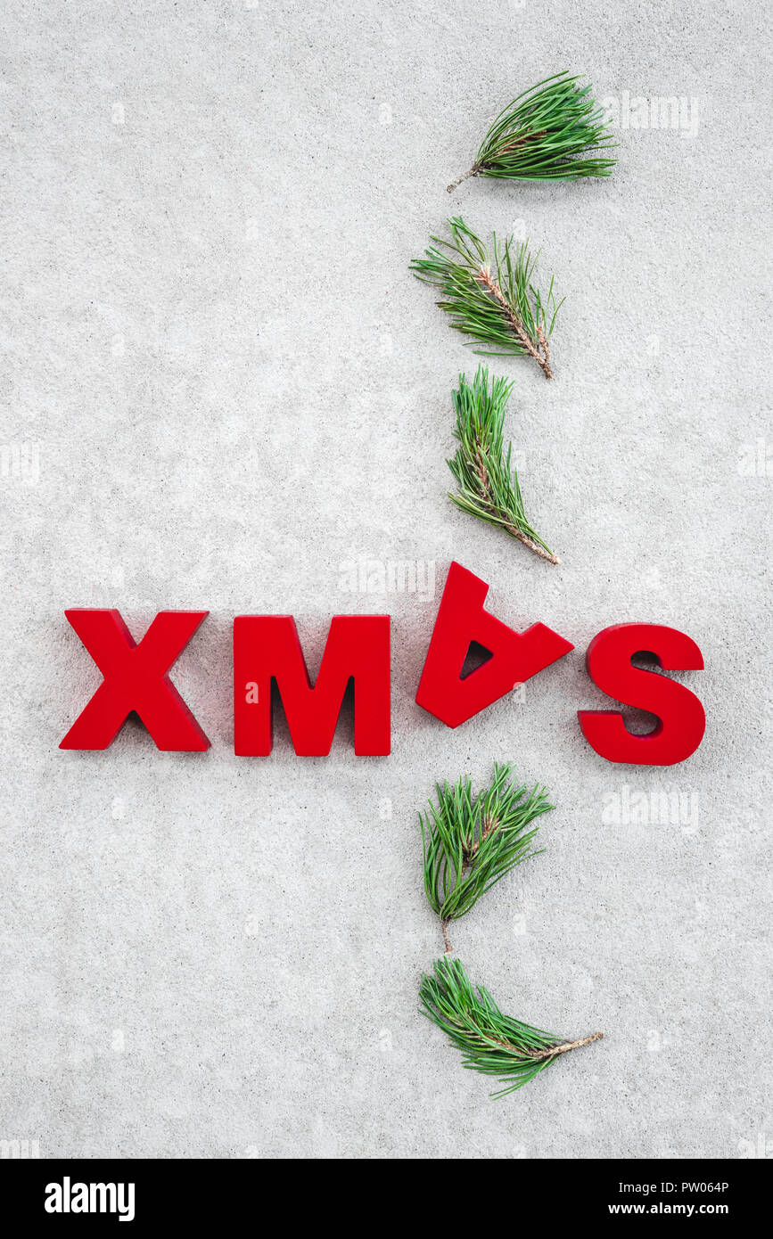Christmas theme. Green pine branches and the word Xmas written upside-down. - Stock Image