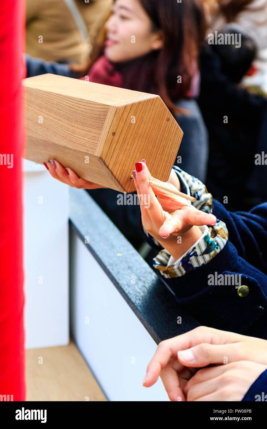 Japanese new year, shogatsu. Close up of young woman hand holding Omikuji box while other hand tugs paper slip out through hole in lid. Ikuta Shrine. - Stock Image