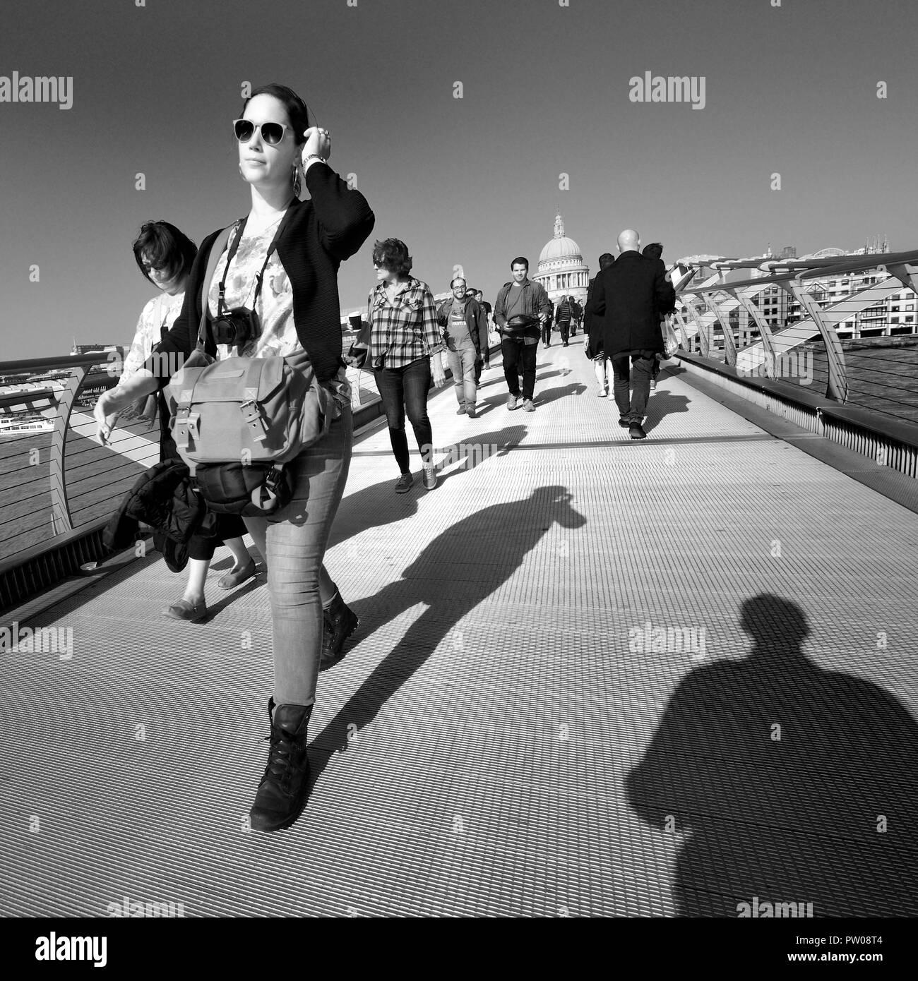 People crossing the Millennium Bridge, London, England, UK. - Stock Image