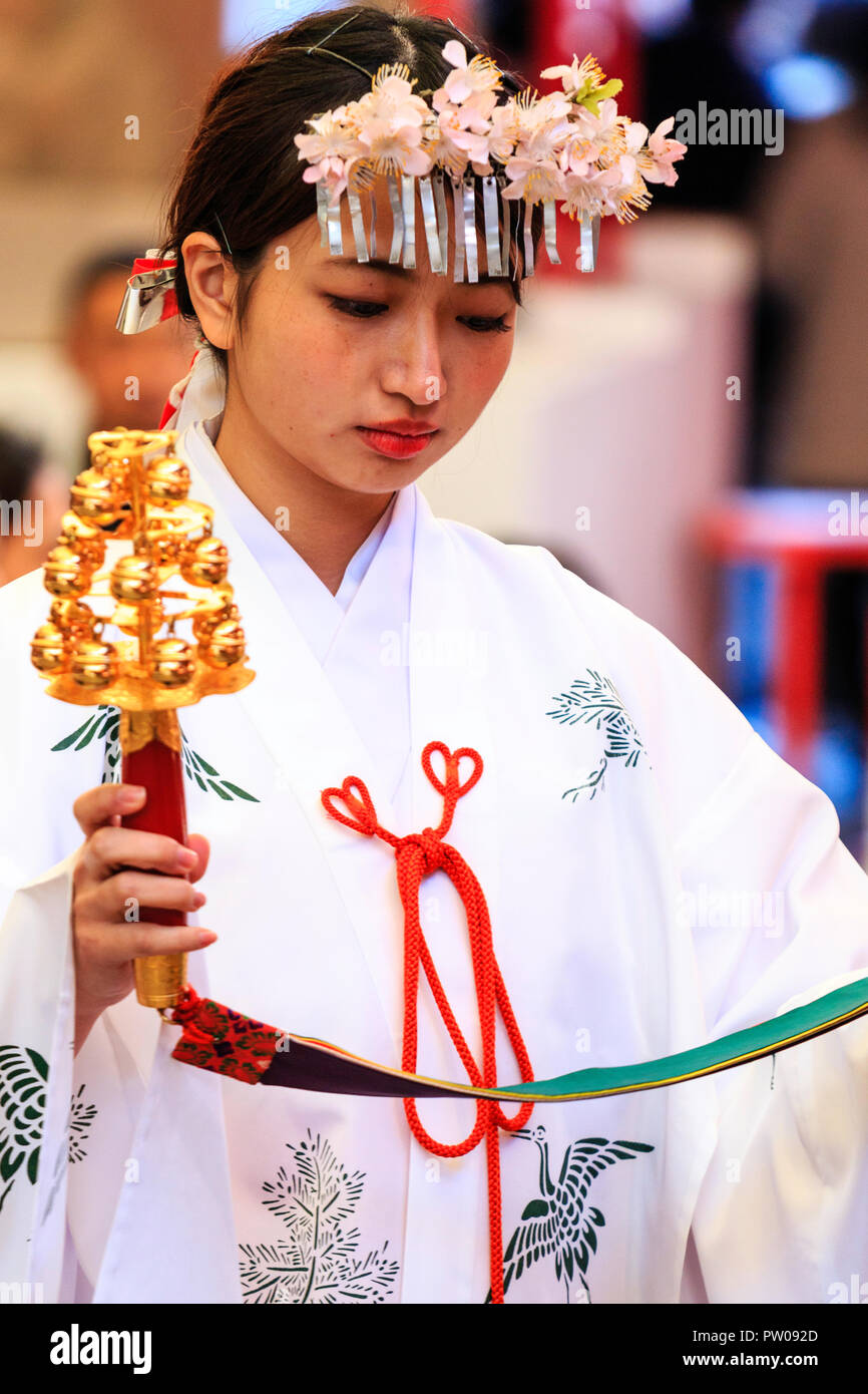 Japanese new year, shogatsu. Shrine Maiden, Miko, with headdress of flowers, performing part of a blessing ceremony at the Ikuta Shinto shrine in Kobe - Stock Image